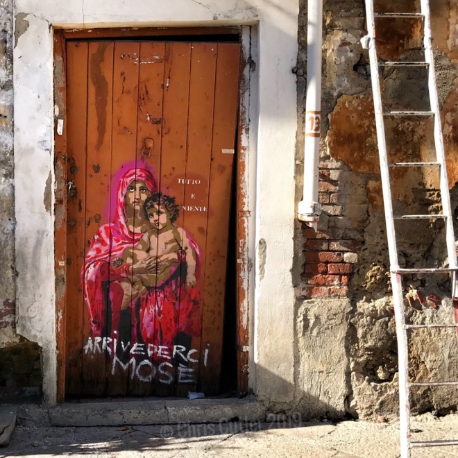 Decaying wooden door with graffiti of Blessed Mother and Jesus