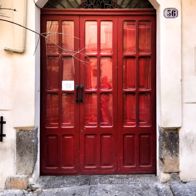 Red door with red glass windows and black handles.