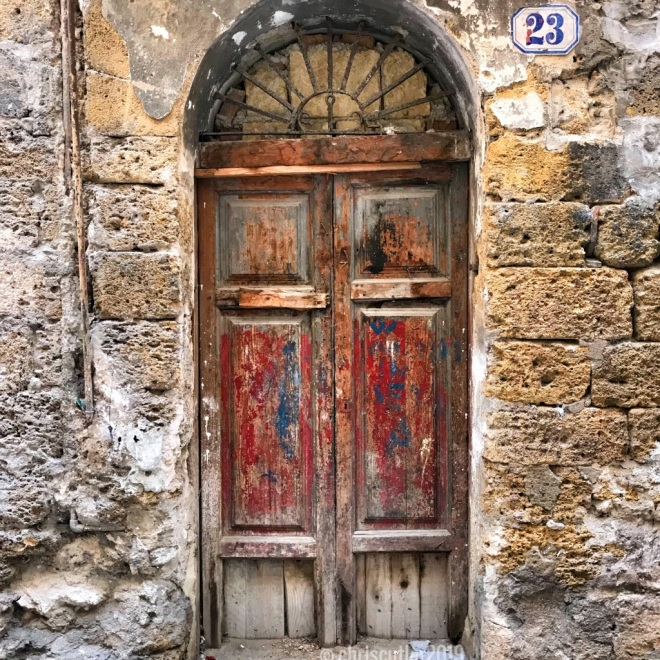 Old wooden door with peeling red and blue paint.