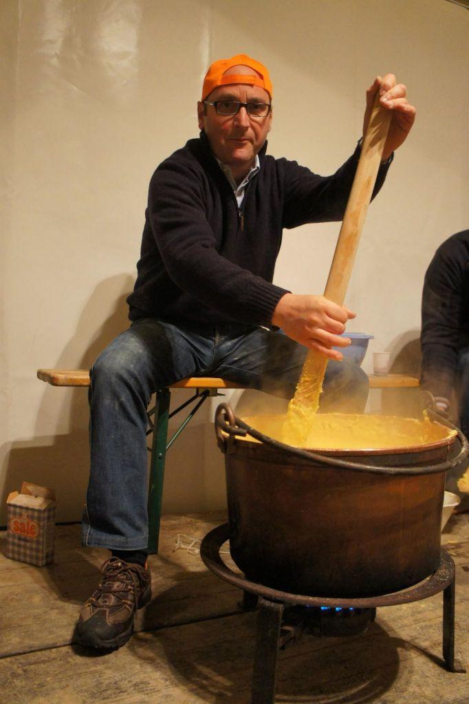A man stirring polenta in a large copper pot