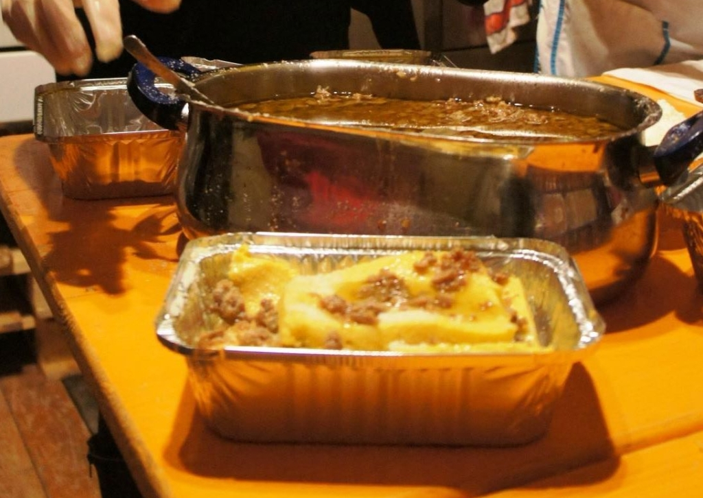 A pan of polenta, sausage, and cheese in front of a pot of sauce