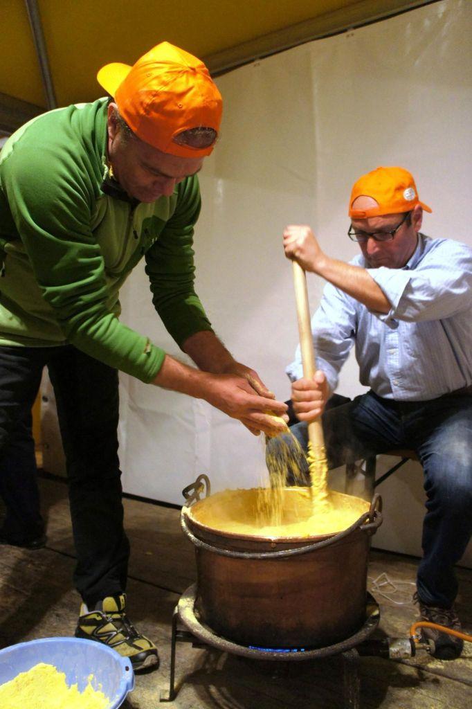One man stirring pot of polenta; second man adding cornmeal to pot