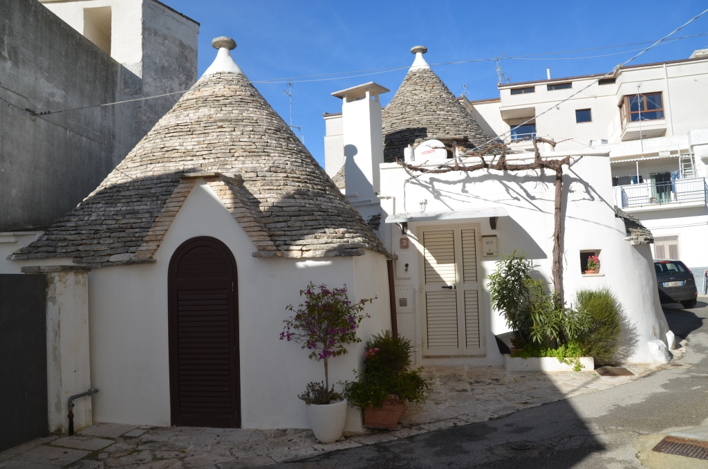Two trulli with modern apartments in the background