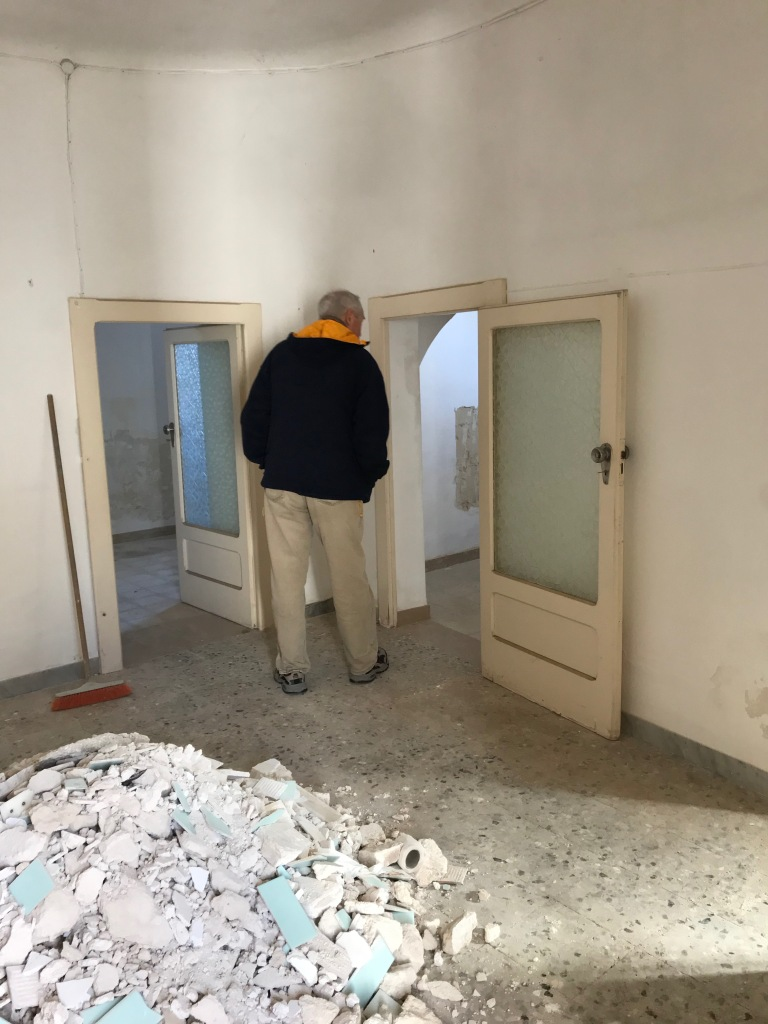 Man looking through door of trullo with pile of trash behind him