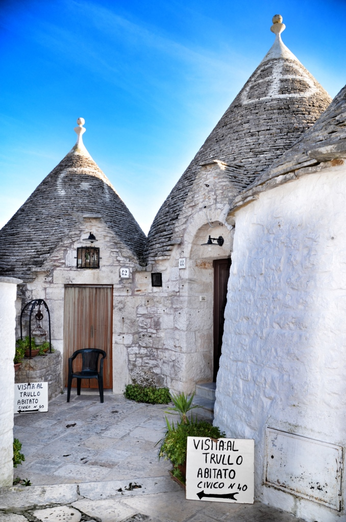 Two trulli with signs inviting tourists to tour an inhabited one