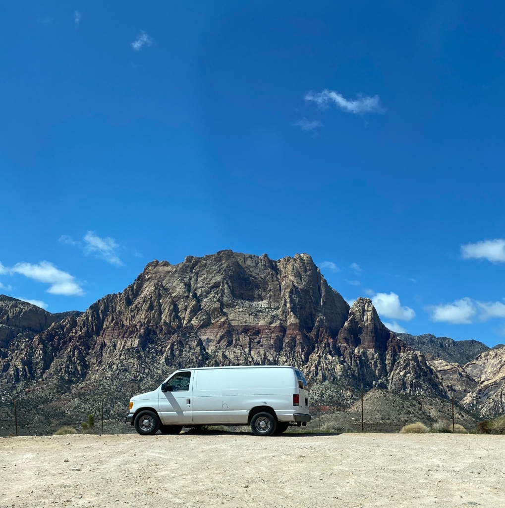 white van, calico mountain behind it, blue sky