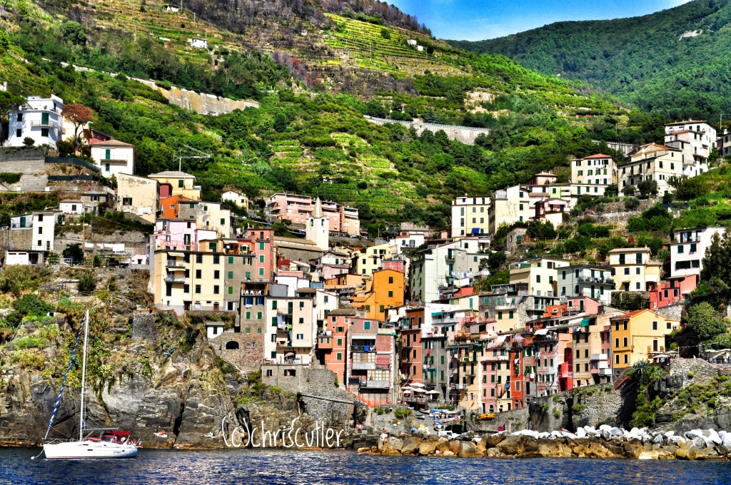 Colorful buildings built along the coastal hills; small boat in foreground